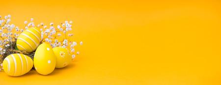 美しいカラフルなイースターエッグ。オレンジまたは黄色の背景に分離されたイースターの概念。