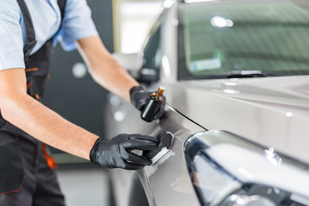 Car detailing - Man applies nano protective coating to the car. Selective focus. Stock Photo