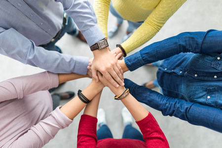 Sluit omhoog hoogste mening van jonge bedrijfsmensen die hun handen samenbrengen. Stapel handen. Eenheid en teamwork concept.