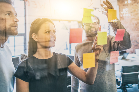 Business people meeting at office and use paper notes to share idea. Brainstorming concept. Sticky note on glass wall. Stock Photo