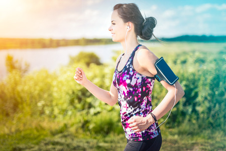Beautiful, young woman running on the waters edge by the country road. Jogging concept.