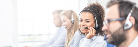 Call center worker accompanied by her team. Smiling customer support operator at work. Young employee working with a headset. Foto de archivo - 111177401
