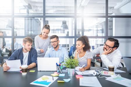 Młodzi ludzie biznesu spotykają się w biurze i wspólnie omawiają nowy projekt startowy.