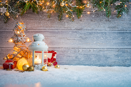 Christmas Card: snowy lantern and candlelight with fir branches and baubles on wooden background. Standard-Bild - 112014410