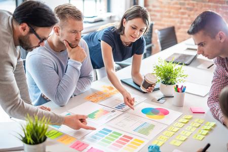 비즈니스 사람들은 사무실에서 회의를 하고 스티커 메모를 사용하여 아이디어를 공유합니다. 브레인스토밍 개념입니다. 유리 벽에 스티커 메모입니다. 스톡 콘텐츠
