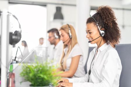 Travailleuse du centre d'appels accompagnée de son équipe. Souriant opérateur de support client au travail. Jeune employé travaillant avec un casque.