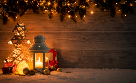 Christmas Card: snowy lantern and candlelight with fir branches and baubles on wooden background.