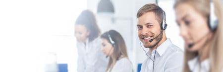 Trabajador de call center acompañado de su equipo. Operador de soporte al cliente sonriente en el trabajo. Empleado joven que trabaja con un auricular. Foto de archivo
