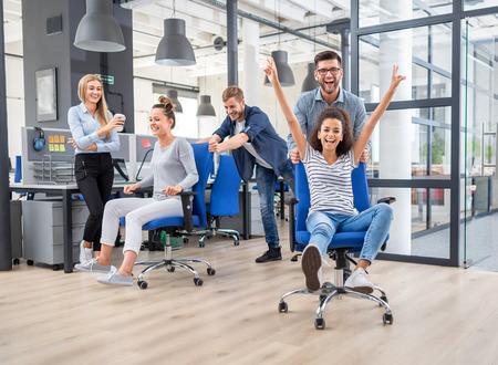 Jonge vrolijke zakenmensen gekleed in casual kleding hebben plezier op roeistoelen in een modern kantoor. Gelukkig teamconcept.