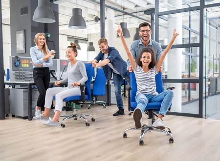 Young cheerful business people dressed in casual clothing are having fun on rowing chairs in a modern office. Happy team concept. 스톡 콘텐츠 - 112532219