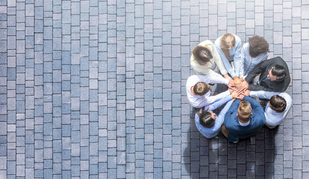 Close up top view of young business people putting their hands together. Stack of hands. Unity and teamwork concept. Archivio Fotografico - 112532240