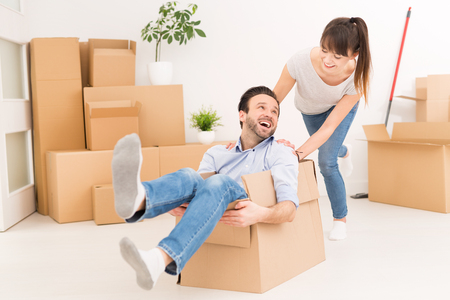 Young couple people have fun while moving to a new apartment. Boy pushes box with the girl. Happy people in the new house. Stock Photo