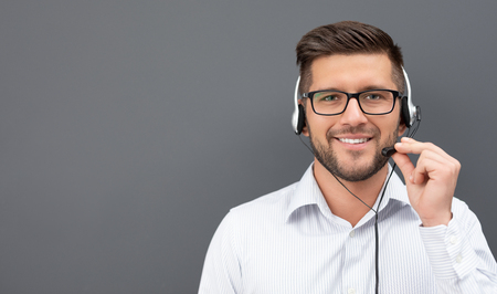 Call center worker isolated on a gray background. Smiling customer support operator at work. Young employee working with a headset.