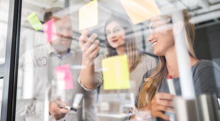 Ludzie biznesu spotykają się w biurze i używają notatek, aby dzielić się pomysłami. Koncepcja burzy mózgów. Karteczkę na szklanej ścianie.