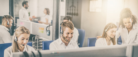 Callcentermedewerker vergezeld door zijn team. Glimlachende klantenondersteuningsoperator op het werk. Jonge werknemer die met een hoofdtelefoon werkt.