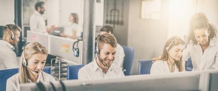 Pracownik call center w towarzystwie swojego zespołu. Uśmiechnięty operator obsługi klienta w pracy. Młody pracownik pracujący z zestawem słuchawkowym.