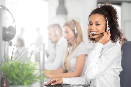 Travailleuse du centre d'appels accompagnée de son équipe. Souriant opérateur de support client au travail. Jeune employé travaillant avec un casque. Banque d'images
