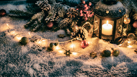 Christmas Card: snowy lantern and candlelight with fir branches and baubles.