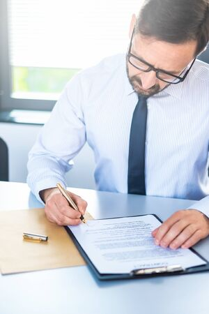 Business man signing contract document on office desk, making a deal. Stock Photo - 125868418