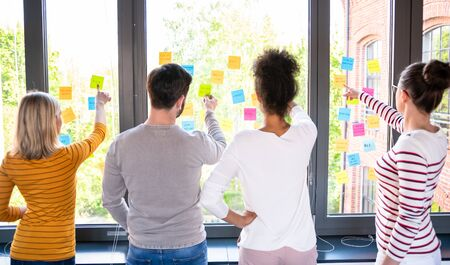 Business people meeting at office and use post it notes to share idea. Brainstorming concept. Sticky note on glass wall. Stok Fotoğraf