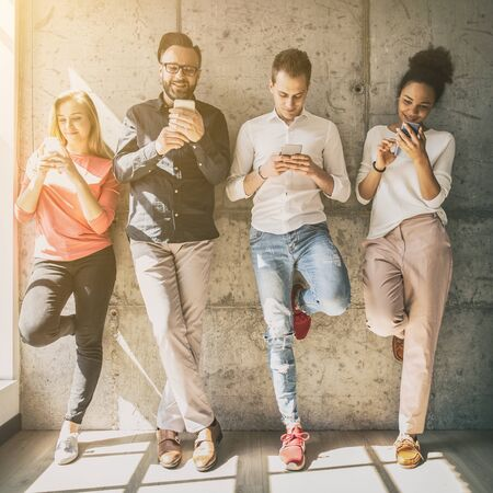 Group of multiracial students and friends watching smart mobile phones. New technology trend. Stock Photo