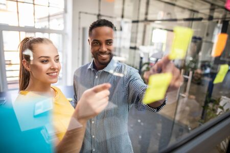 Business people meeting at office and use post it notes to share idea. Brainstorming concept. Sticky note on glass wall. Stock Photo