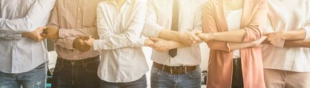 Creative team meeting hands together in line. Young business people are holding hands. Unity and teamwork concept. Stock Photo