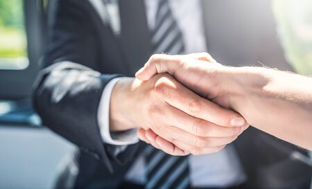 Business people shaking hands, finishing up meeting. Successful businessmen handshaking after good deal. Фото со стока