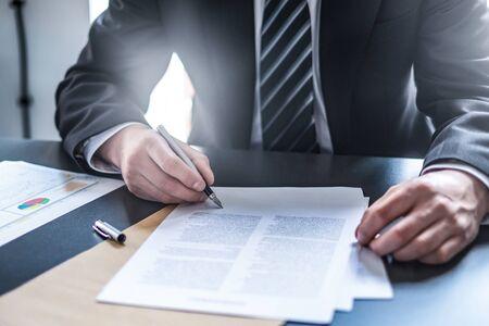 Geschäftsmann, der Vertragsdokument auf Schreibtisch unterschreibt und einen Deal macht.