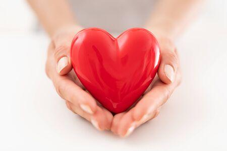 De vrouw houdt een rood hart vast. Concept voor liefdadigheid, ziektekostenverzekering, liefde, internationale cardiologiedag.