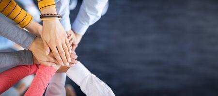 Schließen Sie herauf Draufsicht der jungen Geschäftsleute, die ihre Hände zusammenstellen. Stapel Hände. Einheits- und Teamwork-Konzept. Standard-Bild