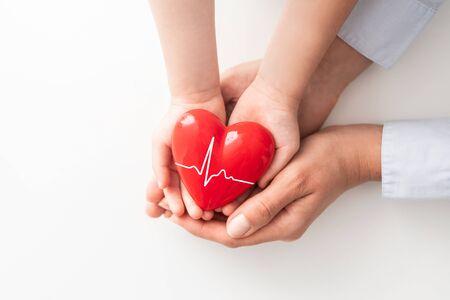 Ein Erwachsener, eine Mutter und ein Kind halten ein rotes Herz in ihren Händen. Konzept für Wohltätigkeit, Krankenversicherung, Liebe, internationaler Kardiologietag.