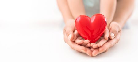 An adult, mother and child hold a red heart in their hands. Concept for charity, health insurance, love, international cardiology day. Reklamní fotografie