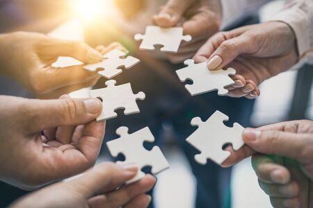 Eine Gruppe von Geschäftsleuten, die Puzzle zusammenbauen. Das Konzept der Zusammenarbeit, Teamarbeit, Hilfe und Unterstützung im Geschäft.