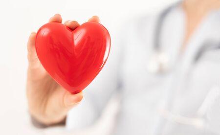 De dokter houdt en toont een rood hart. Concept voor onderwerpen: gezondheid, ondersteuning, internationale of nationale cardiologiedag.