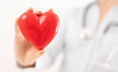 Le médecin tient et montre un cœur rouge. Concept pour les sujets : santé, soutien, journée internationale ou nationale de cardiologie.