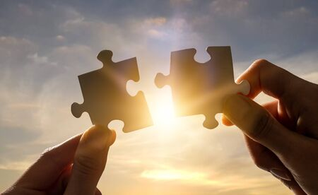 The man holds in his hand a jigsaw puzzle. Business solutions, success and strategy concept.