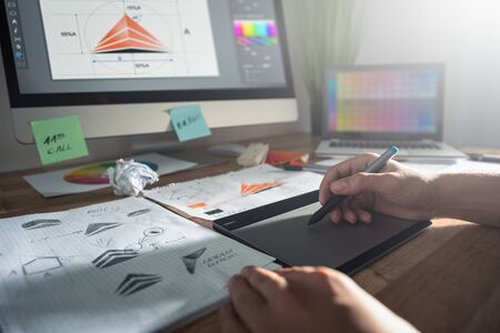 Graphic designer drawing sketches logo design. The concept of a new brand. Professional creative occupation with idea. Stock Photo