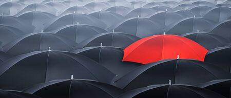 Different and standing out of the crowd yellow umbrella. Concept of leader with many blacks umbrella.