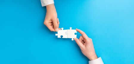 The man and woman holds in hand a jigsaw puzzle. Business solutions, success and strategy concept.