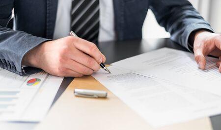 Uomo d'affari che firma il documento del contratto sulla scrivania dell'ufficio, facendo un accordo. Archivio Fotografico