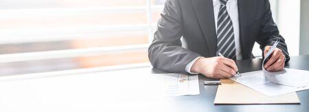 Homme d'affaires signant un document contractuel sur un bureau, concluant un accord.