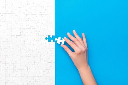 Hand put the last piece of jigsaw puzzle. Complete the mission. Business concept.