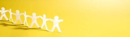 Team of paper chain people. Human chain with light and shadow. Yellow tone background.