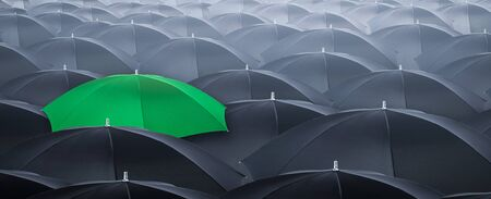 Different and standing out of the crowd yellow umbrella. Concept of leader with many blacks umbrella. Stock Photo