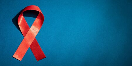 Red ribbon symbol of awareness AIDS and HIV disease. International World AIDS Day.