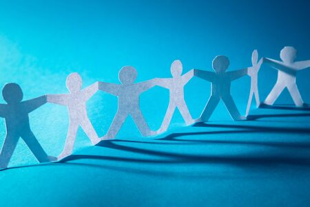 Team of paper chain people. Human chain with light and shadow. Blue tone background.