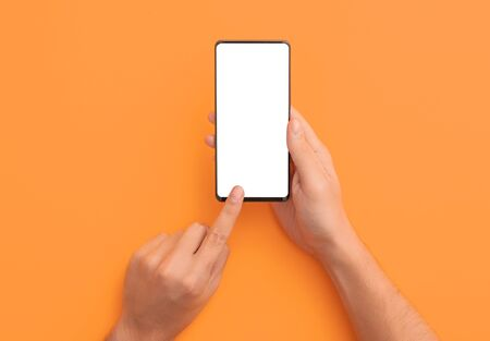Hand holding black phone isolated on orange background and clipping path inside. Smartphone mock up concept.