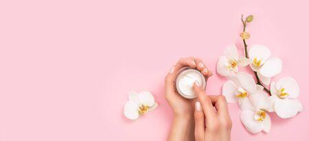 Woman applying moisturizing cream on hands. Cosmetic cream lotion concept.