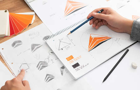 Graphic designer drawing sketches logo design. The concept of a new brand. Professional creative occupation with idea.